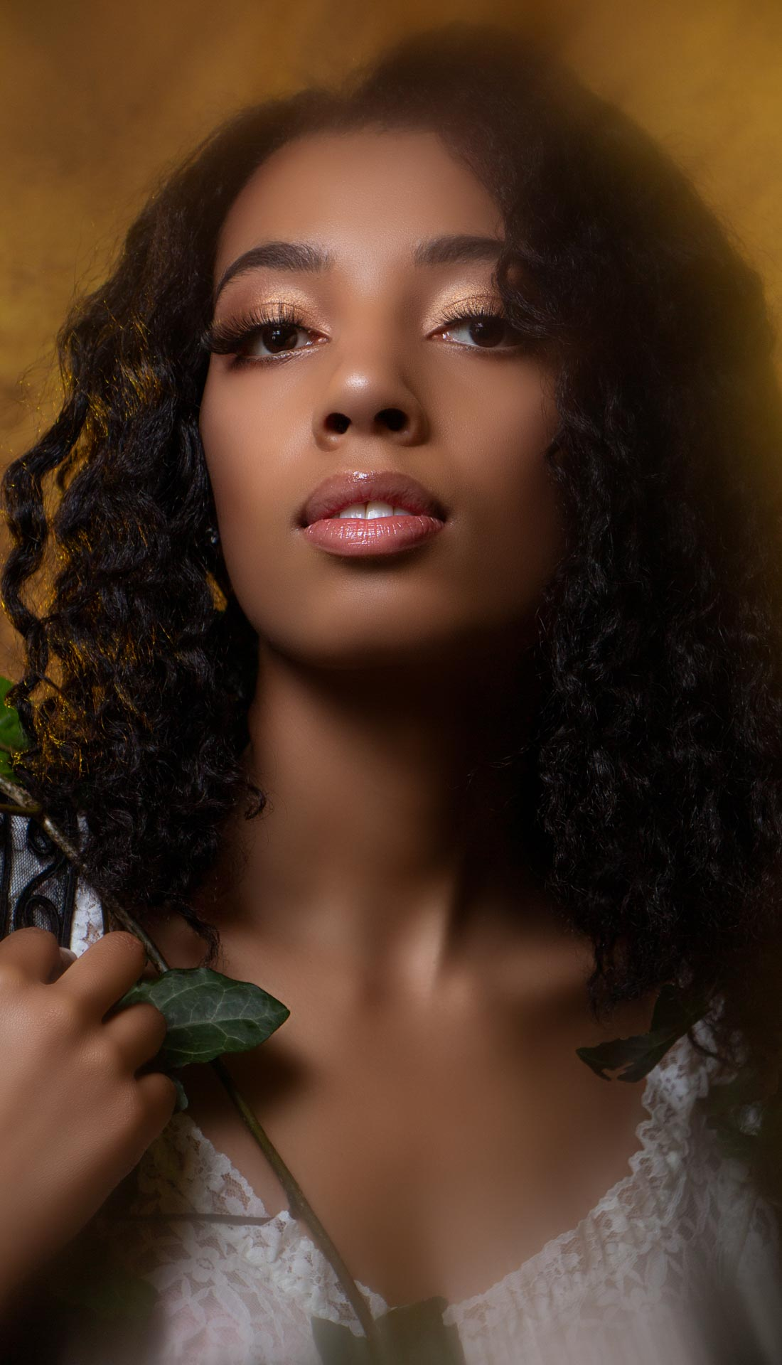 A beauty portrait of a black woman posing with ivy