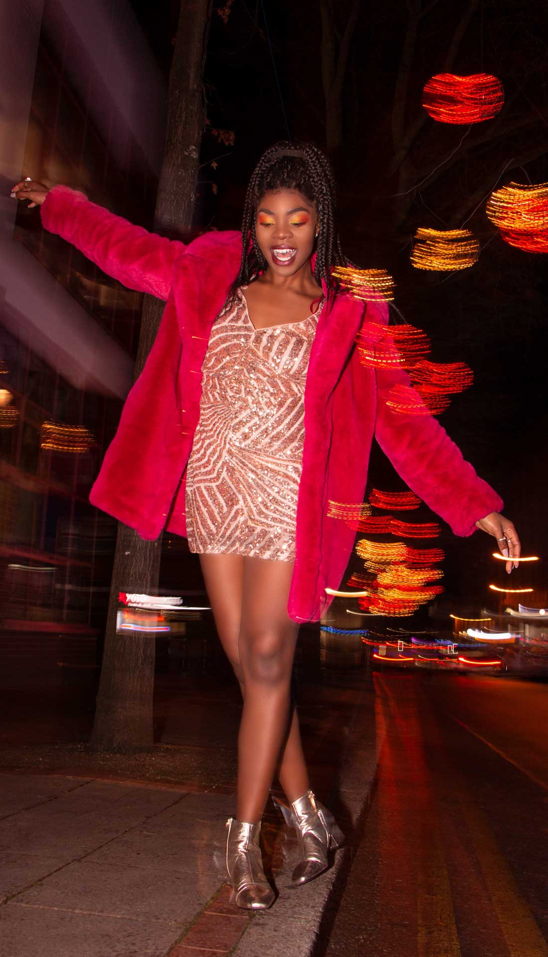 A black woman wearing glitter dress and pink fur is balancing on the curb in night Birmingham, U.K.