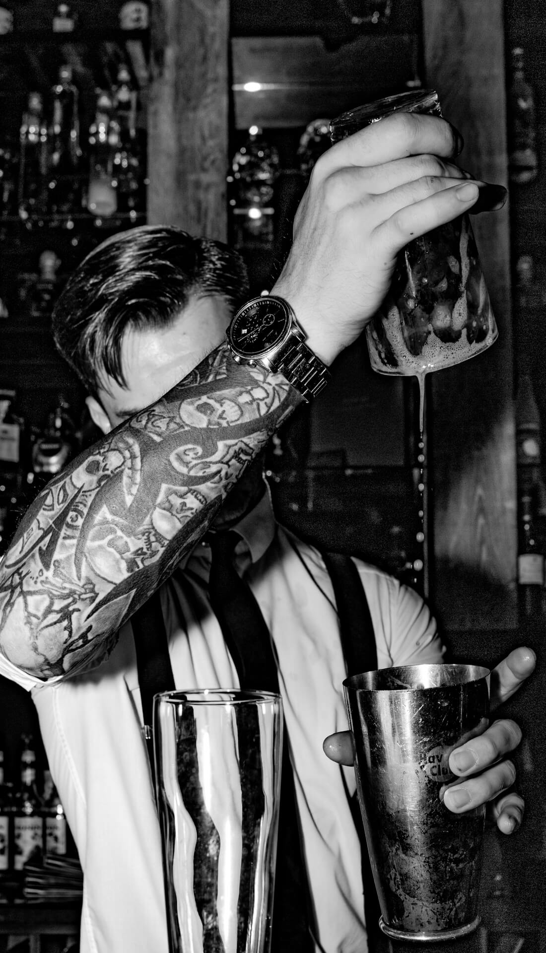 Action image of a tattooed bartender making a drink. Marketing photography for food and drink caterer in Birmingham UK