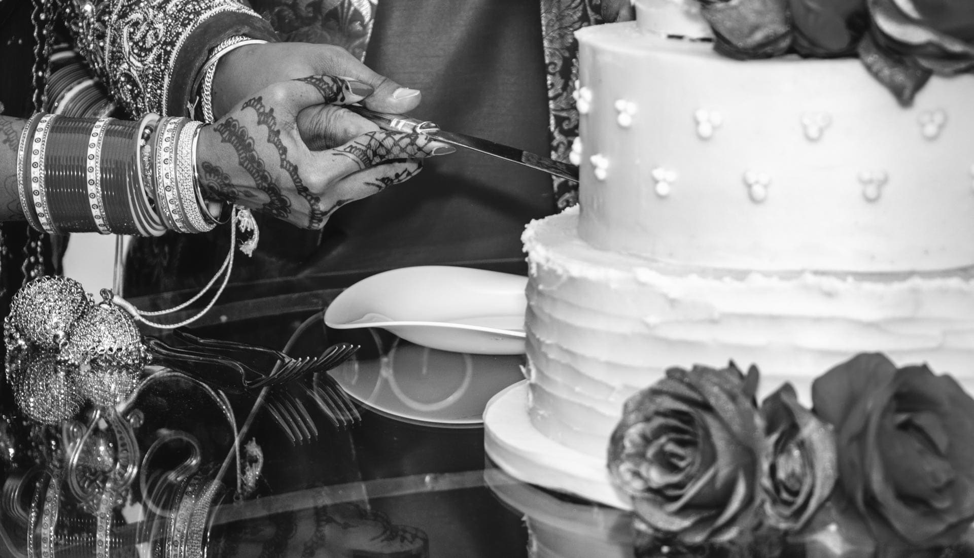 Cutting cake detail photo, Asian bride and groom hands are holding a knife cutting their wedding cake, documentary wedding photographer Birmingham uk