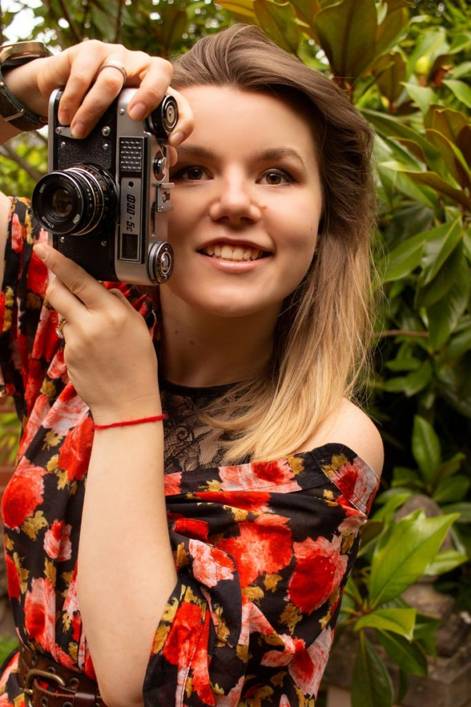 Photographer Anastasia Jobson is holding FED 5 film camera ready to take a photo. How to use tiktok as a photographer