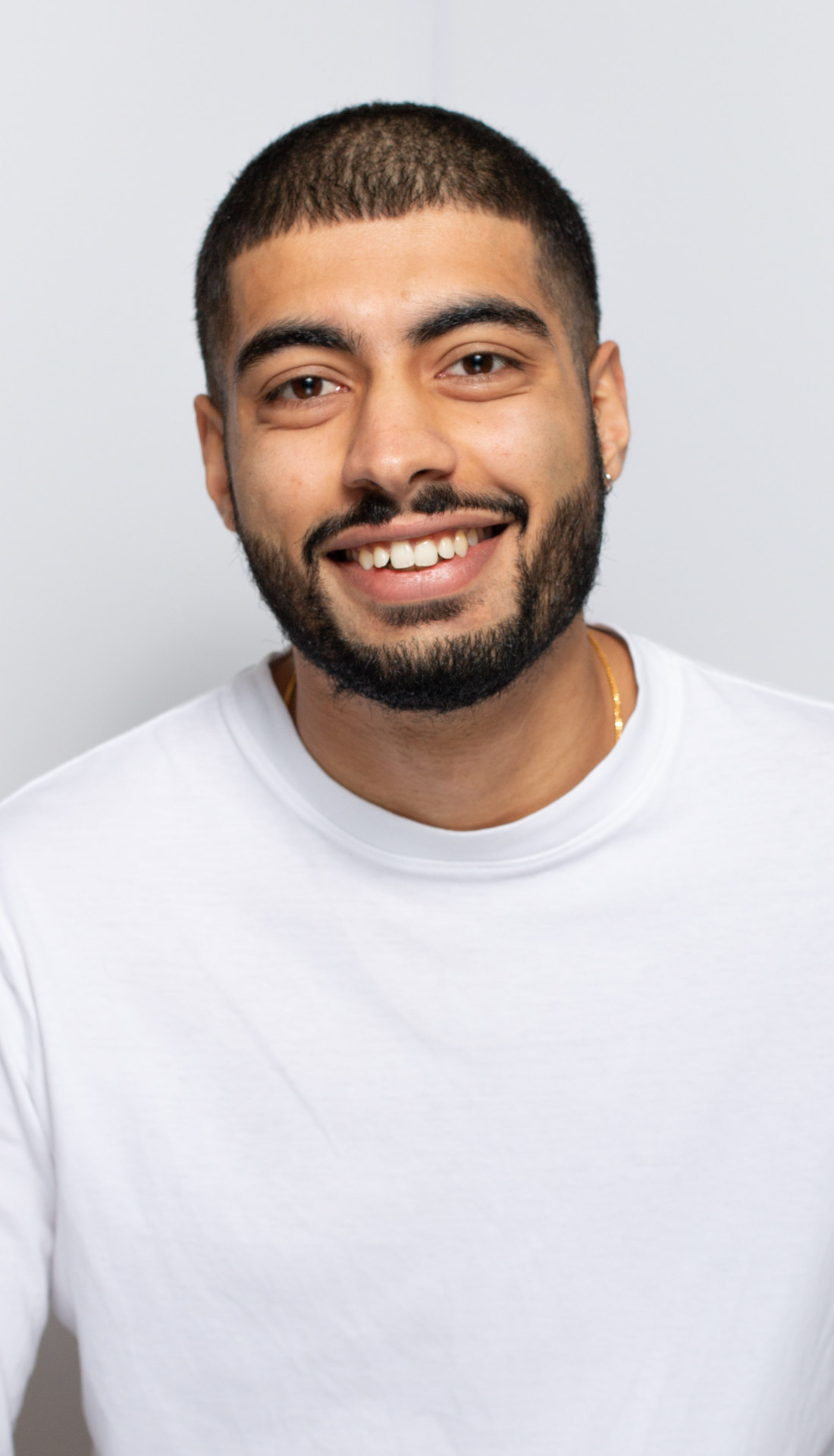 Simple white background headshot of a man wearing a white top smiling