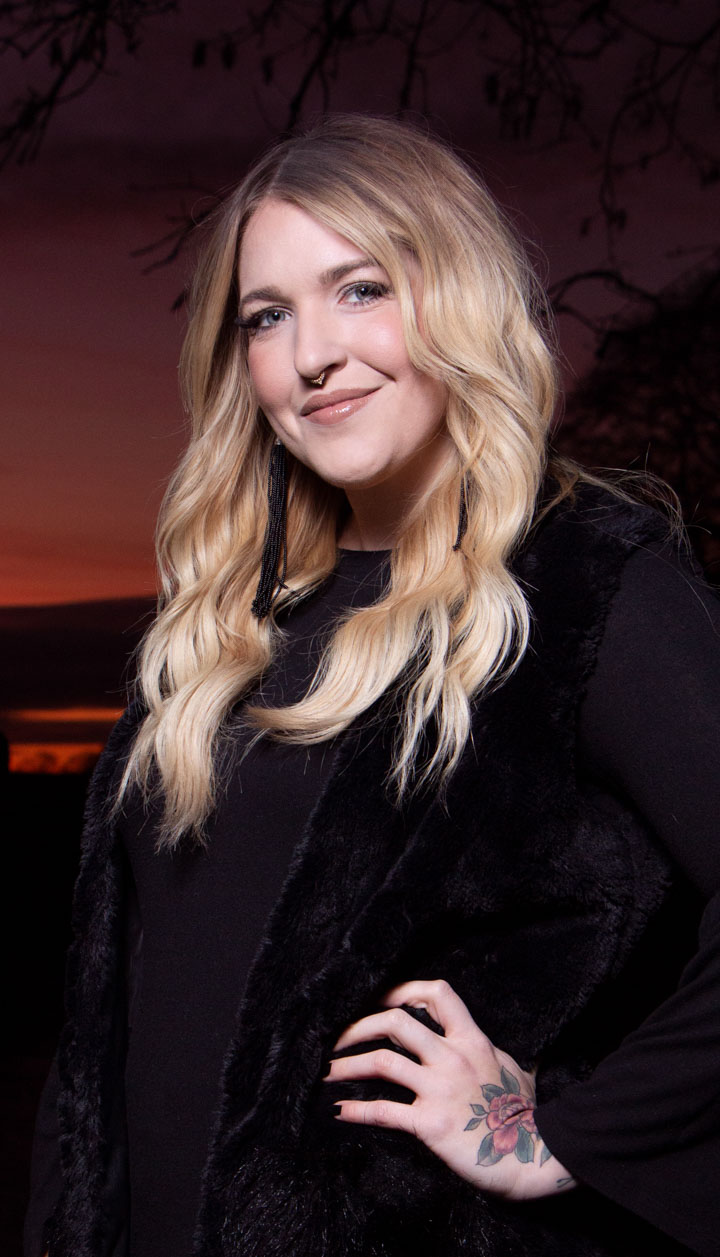A business headshot of a blond woman wearing all black and posing in front of sunset