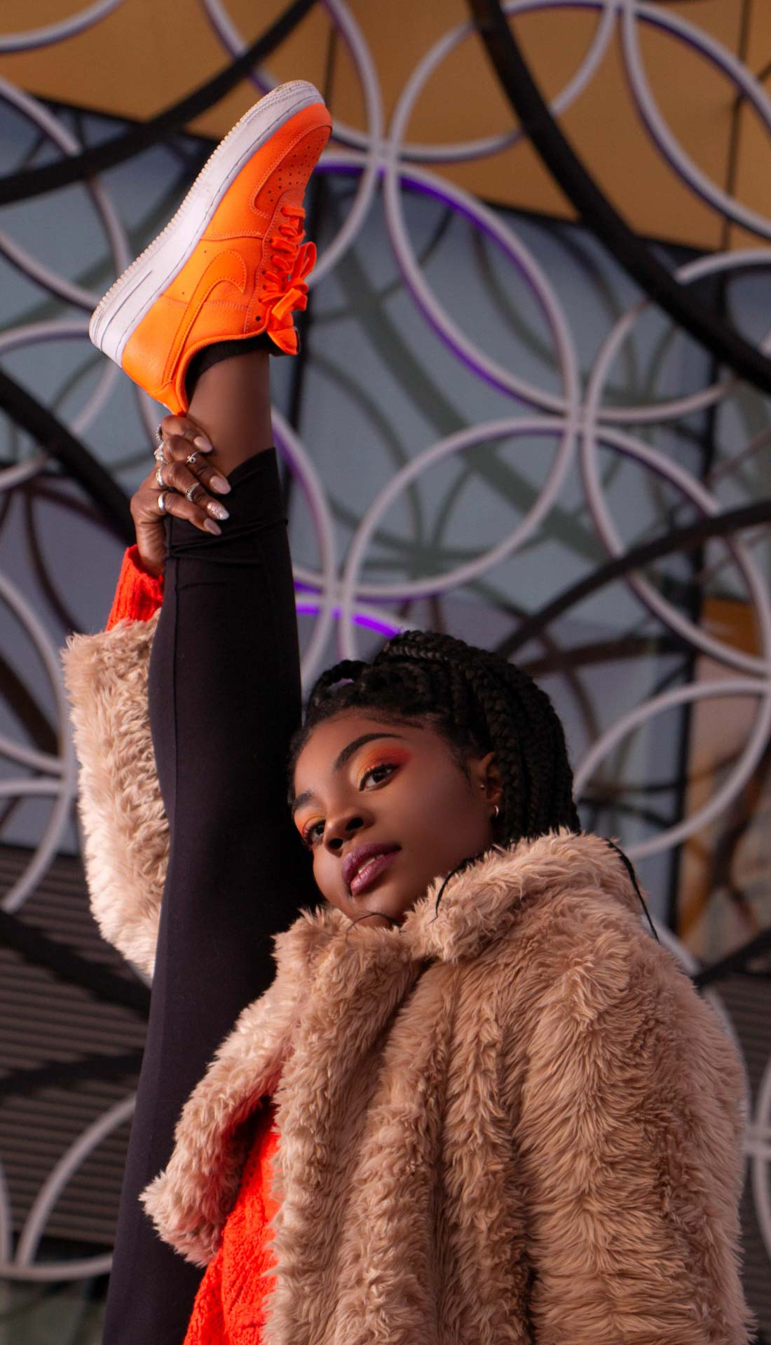 Birmingham street dancer posing her orange Nike shoes while stretching her leg in a split