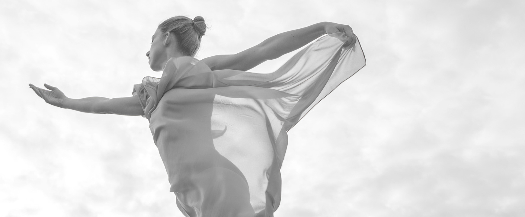 Ballerina dancing on the beach with translucent scarf wrapped around her body. Creative ballet dance photography