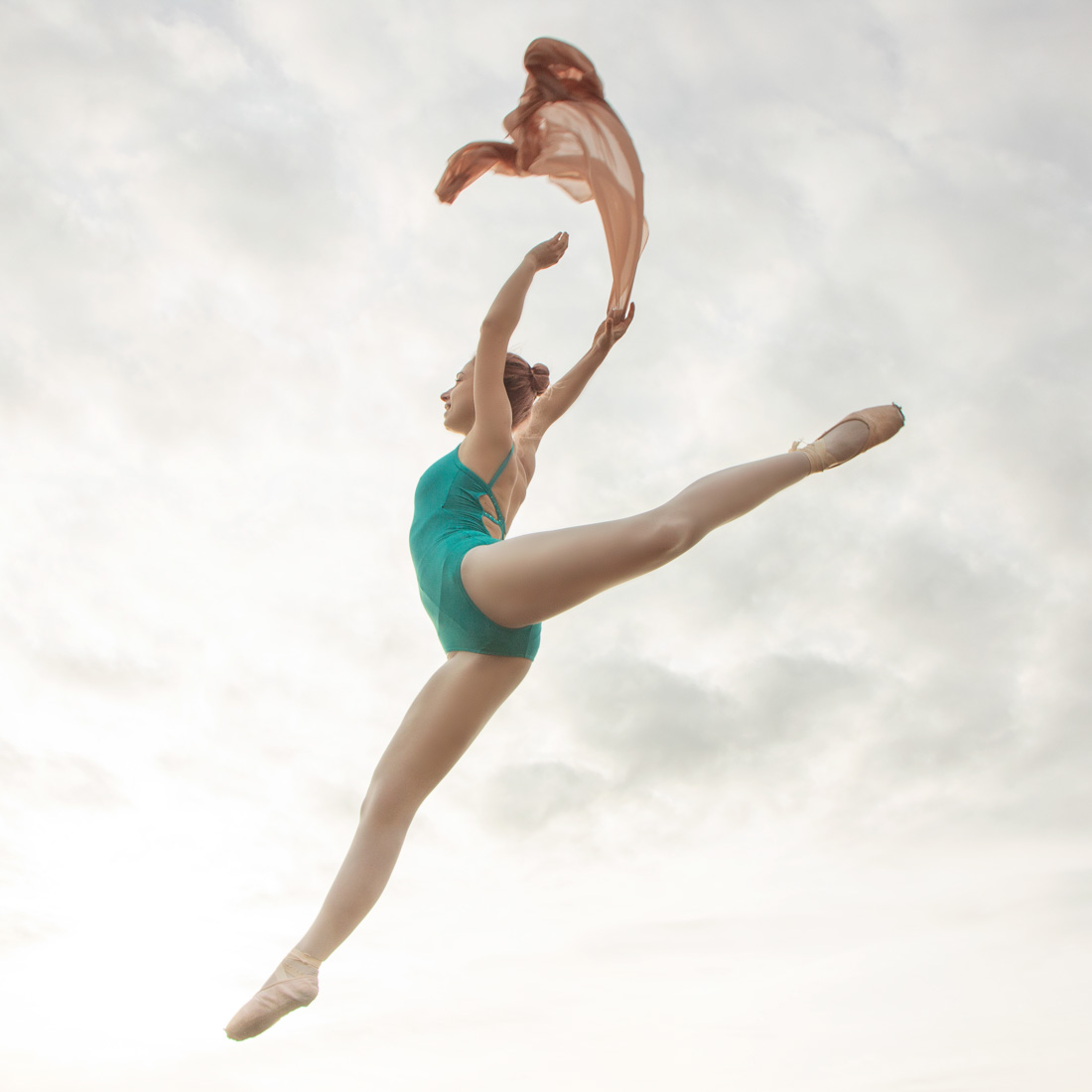 Ballerina in a turquoise leotard is jumping while holding a beige colour scarf. Creative ballet dance photography