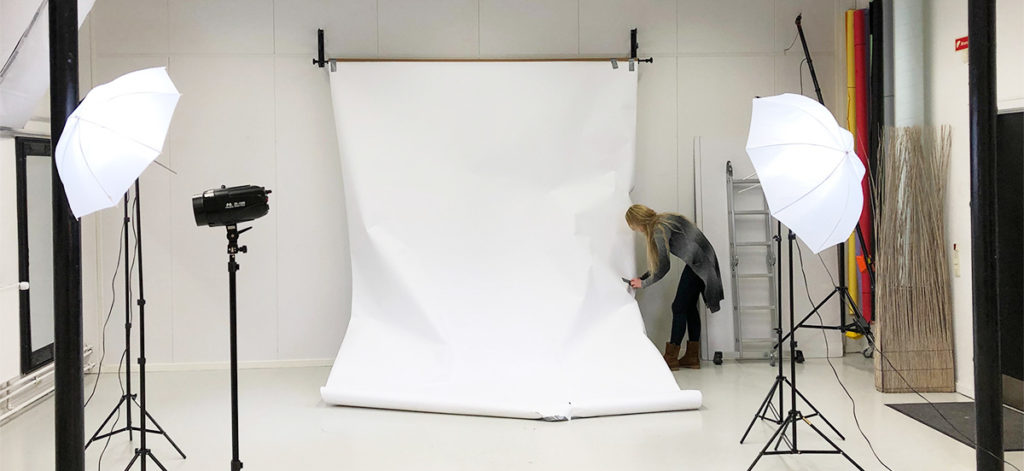 blond woman is setting up white backdrop for a photoshoot