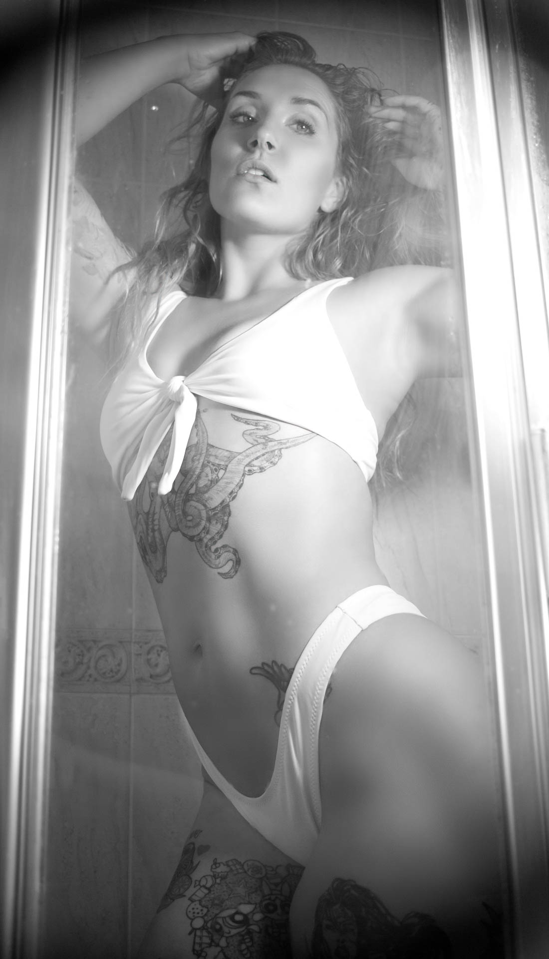A blond tattooed woman is posing in the shower in white bikini swim suit