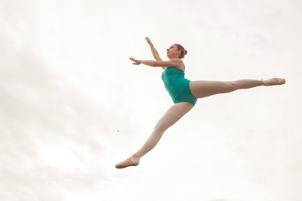 A ballet dancer wearing turquoise leotard is striking a pose in the air