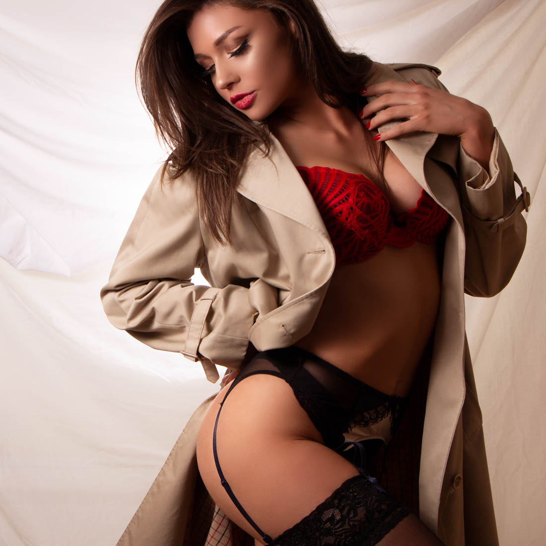 Brown hair woman wearing a vintage trench coat and red and black lingerie