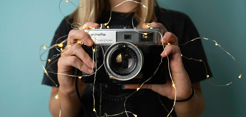 A blond woman is standing in front of blue wall, holding Minolta film camera ready to take a photo, with fairy lights surrounding camera.