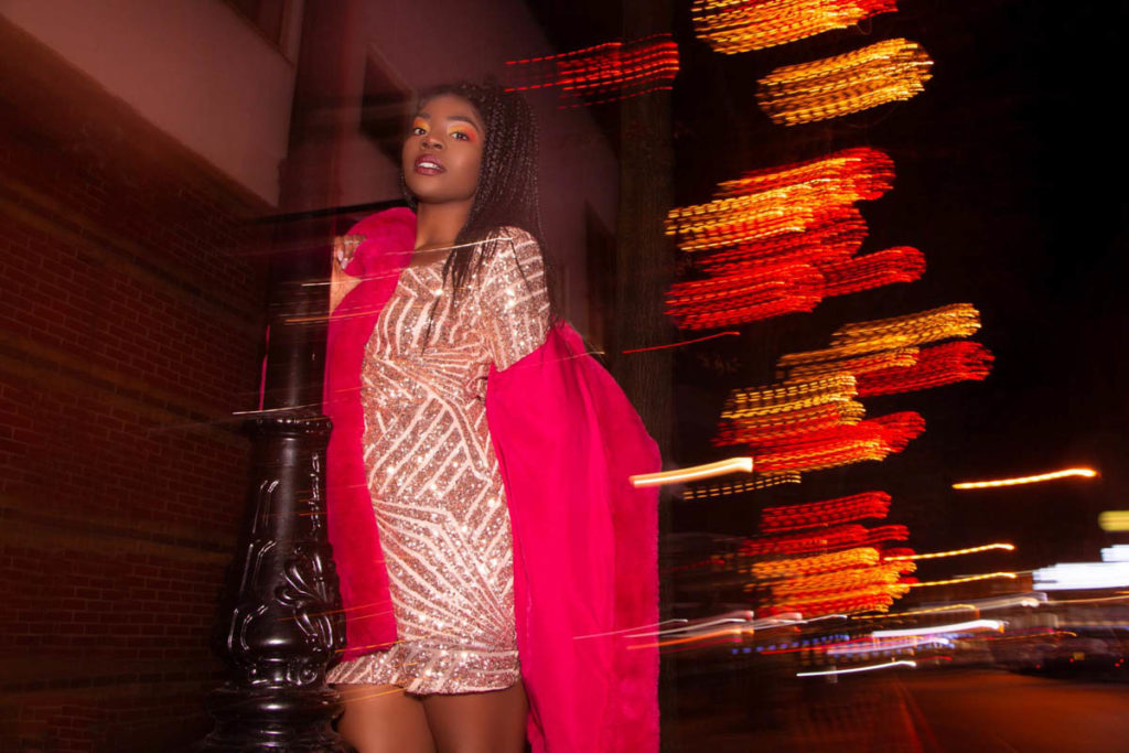 A black woman in sparkly dress is taking bright pink fur coat off her shoulder on a street at night