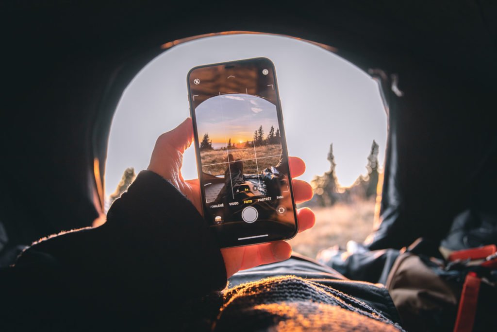 A hand holding iPhone and taking photo of sunset. how to get good lighting for TikTok