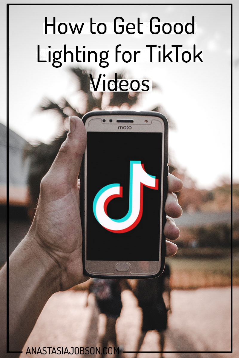 Man's hand holding phone with TikTok icon on. How to get good lighting for your TikTok videos