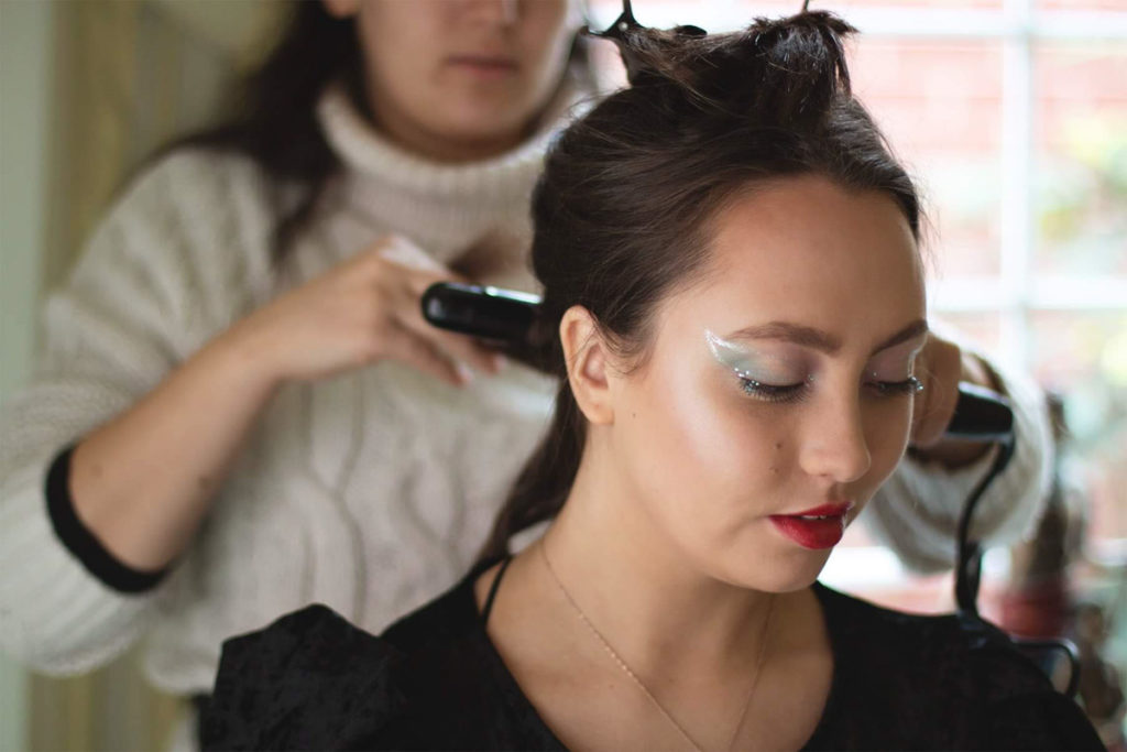 A woman is having her hair done for a photoshoot. Make up and hair by Eleonora Manzi, Photo by Anastasia Jobson