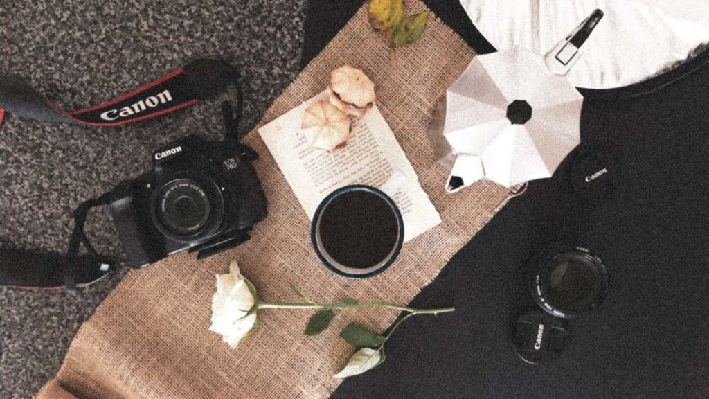 a flatlay image with canon camera, coffee and camera lenses. Business tips for photographers during covid-19