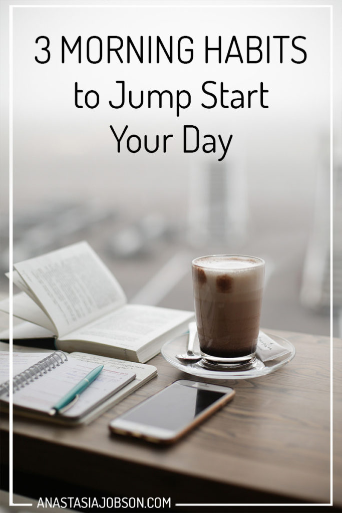 A wooden table with an open book, planner with a blue pen lying on top, a glass of cappuccino and a phone. Text saying 3 morning habits to jump start your day.