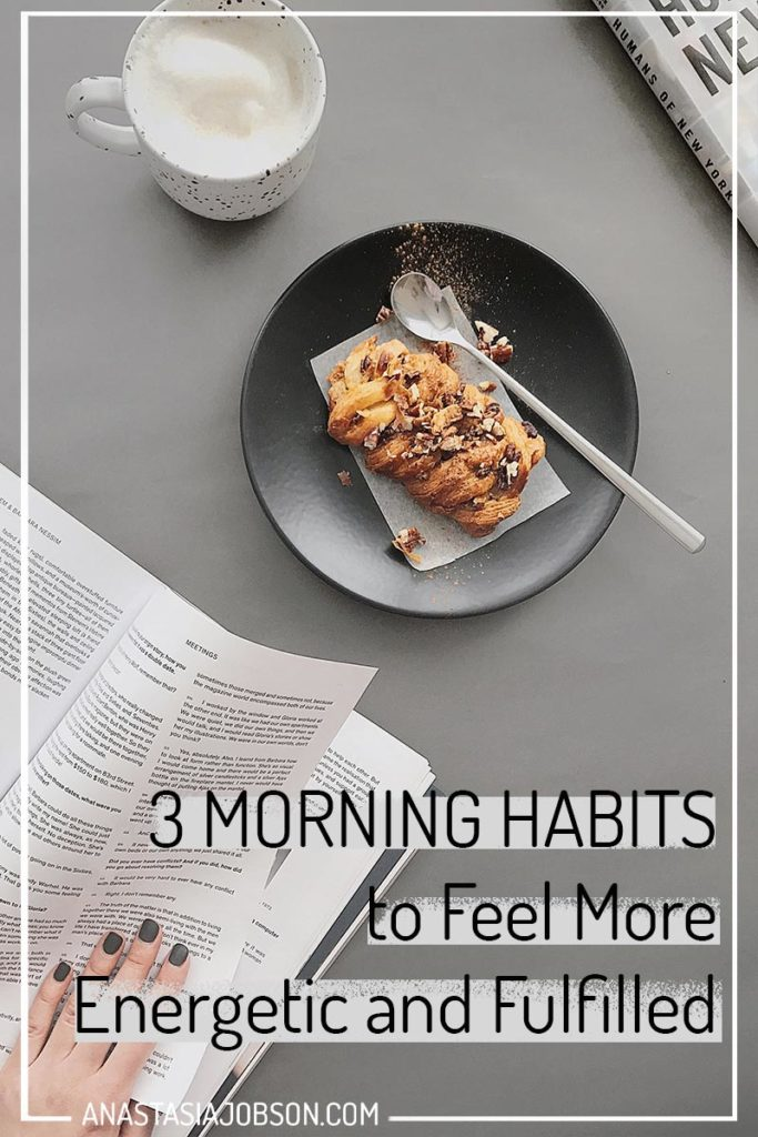 A dark grey plate with a pastry on a light grey table and woman's hand flicking through a book. Text saying 3 morning habits to feel more energetic and fulfilled
