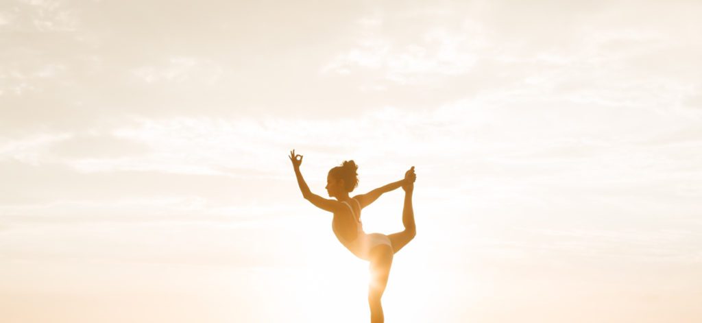 Woman wearing a swimsuit is striking yoga dancer's pose during golden hour with sky as a background
