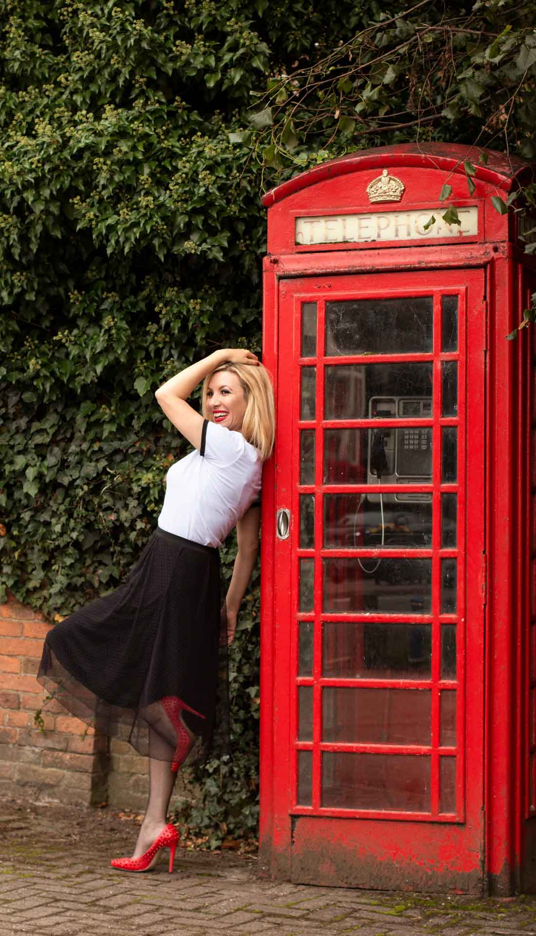 Blond woman posing next to red telephone booth. Personal branding photography Birmingham UK, Birmingham fashion designer Rossi Videnova, branding photographer West Midlands
