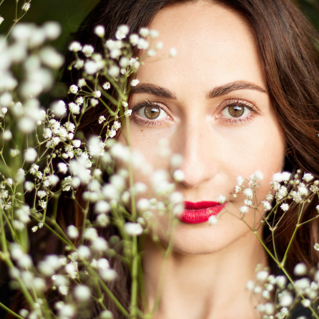 A close-up portrait of a woman with white flowers. Portrait photographer Birmingham UK, personal photoshoots in Birmingham and West Midlands, professional photography services in West Midlands UK